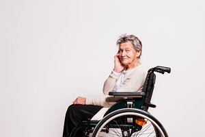 Portrait of a senior woman with wheelchair in studio.
