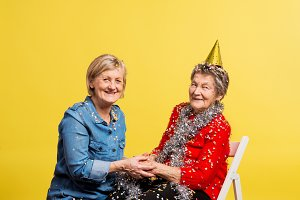 Portrait of a senior women in studio on a yellow background. Party concept.
