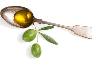 Olive oil and twig with olives.