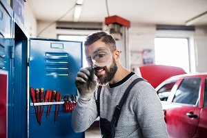 Portrait of a man mechanic in a garage, using magnifying glass.