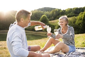 Senior couple at the lake having a picnic.