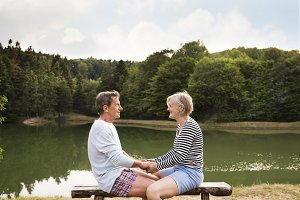 Senior couple sitting on a bench at the lake.