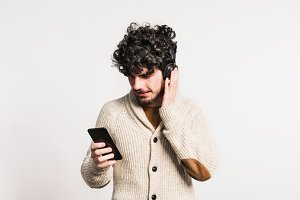 Portrait of a young man with smartphone and headphones in a studio.