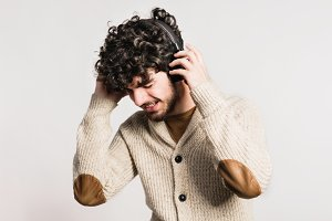Portrait of a young man with headphones in a studio.
