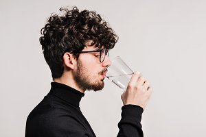 Young man in a studio, drinking water.