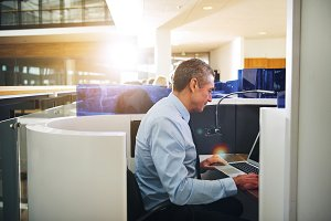 Mature office manager using laptop at workplace
