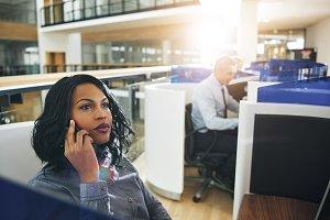Dreamy black woman talking smartphone in office