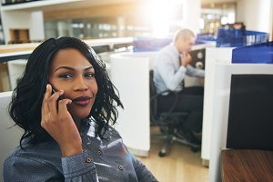 Pretty black office employee sitting and talking smartphone