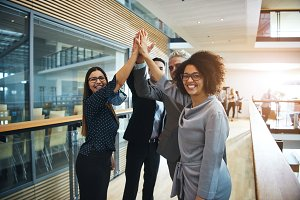 Multiethnic business people giving high five in office