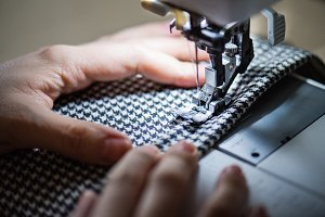 Young woman using sewing machine, startup business.