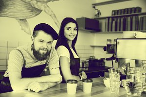 Coffee Business Concept - Positive young bearded man and beautiful attractive lady barista couple in apron looking at camera while standing at bar Counter
