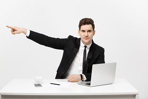 Business Concept: Portrait of handsome businessman dressed in suit sitting in office pointing finger at copy space and laptop isolated over gray background