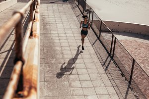 Female athlete running on seaside