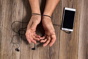 hands of man tied with phone headset, as the concept of man's dependence on music, technology