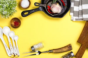Various kitchen utensils on yellow background