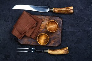 Wooden cutting board, bowl for spices and vintage fork and knife on stone black background