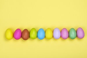 Row of bright colorful easter eggs on sunny yellow background