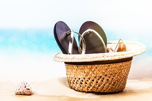 Beach straw hat, flip flops and sun glasses on the sandy beach near the ocean