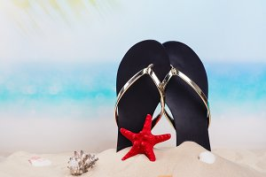 Beach flip flops on the beautiful sandy beach near the ocean. Copy space