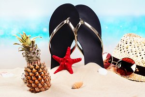 Beach flip flops, hat and sunglasses on the beautiful sandy beach near the ocean. Copy space