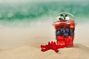 Plastic cup full of fresh cut fruits and berries