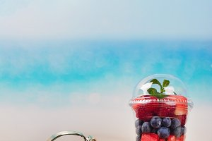 Flip flops and plastic cup with cut fruits and berries on the sea coast