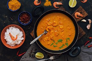 Curry sauce with shrimps in a frying pan. Rice in a bowl, spices, lime.Thai, Indian food. View from above.