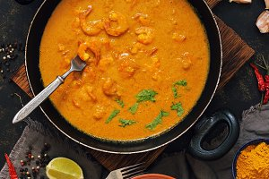 Asian food shrimp in curry sauce, rice and spices.Indian or Thai dish. View from above.
