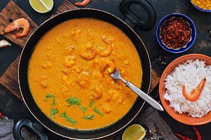 Shrimps with curry sauce in a frying pan on a dark background. . Thai , Indian dish. Asian food.
