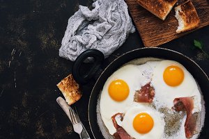 Fried eggs and bacon in a frying pan, dark rustic background. Top view, copy space.