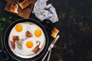 Three fried eggs with bacon in a frying pan with toast, dark rustic background. Top view, space for text.