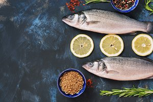 Fresh fish sea bass and ingredients for cooking - lemon, rosemary, bell pepper, sumac, coriander, paprika. Raw fish on a blue background. Top view, copy space.