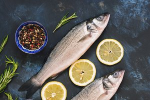 Raw fish with lemon, rosemary and spices on a blue rustic background. Top view, copy space.