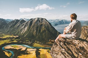 Man sitting on cliff edge relaxing