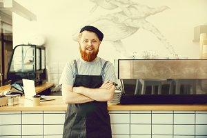 Coffee Business Concept - Positive young bearded man in apron looking at camera while standing at bar Counter