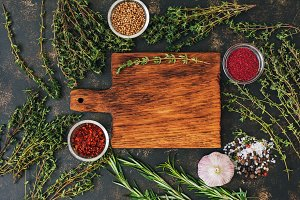 Empty cutting Board with herbs thyme, rosemary and spices. Place for text, top view. Bright beautiful photo.