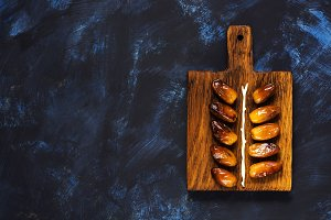 Dates on the cutting board. Honey dates on a blue background, top view, copy space.Oriental fruits