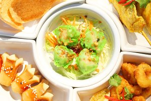 Close up mix delicious appitizer set: Dimsum ,sausace,chicken satay,calamari and rice cracker on white plate