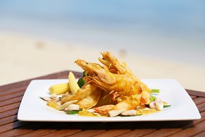 Fried Shrimp on decoration vegetable on wooden table with beach view