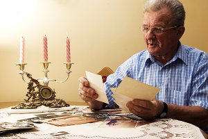 Old man looking at old photographs