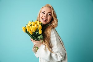 Portrait of a cheerful young blonde woman in sweater
