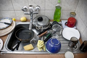 Ordinary sink full of dirty dishes