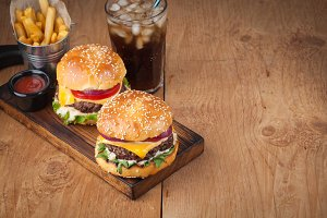Close-up of delicious fresh home made burger with lettuce, cheese, onion and tomato on a rustic wooden board. Also fries and Cola with ice on a wooden table with copy space