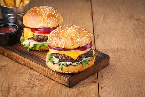 Close-up of delicious fresh home made burger with lettuce, cheese, onion and tomato on a rustic wooden board. Also fries with ketchup on a wooden table with copy space