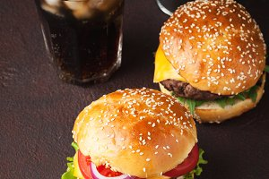 Close-up of delicious fresh home made burger with lettuce, cheese, onion, tomato and cola with ice on a dark background