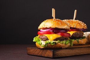 Close-up of delicious fresh home made burger with lettuce, cheese, onion and tomato on a dark background with copy space. fast food and junk food concept