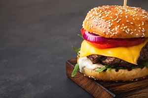 Tasty grilled home made burger with beef, tomato, cheese, cucumber and lettuce on a dark stone background with copy space