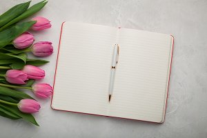 Blank note pad with pen and pink tulips on light stone background