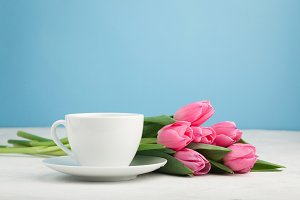 Black coffee in white Cup with pink tulips on light stone background