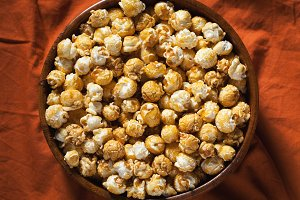 Wooden bowl with sweet popcorn on orange bedding. Snacks and food for a movie. Top view with copy space